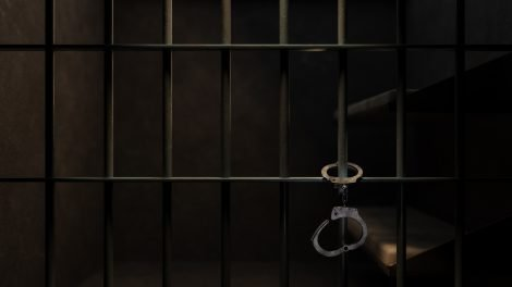 Dimly Lit Prison Cell and Handcuffs